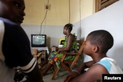 Jean-Noel Kouame joins his family as they watch television inside their house in Abidjan, Ivory Coast, Dec. 18, 2017.
