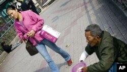 一名妇女走过广州街头的一名乞丐(资料照片)