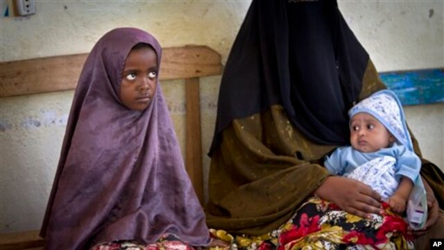 A Somali mother and her older child wait in line for her baby to receive a five-in-one vaccine against several potentially fatal childhood diseases, at the Medina Maternal Child Health center in Mogadishu, Somalia Wednesday, April 24, 2013. (AP Photo/Ben)