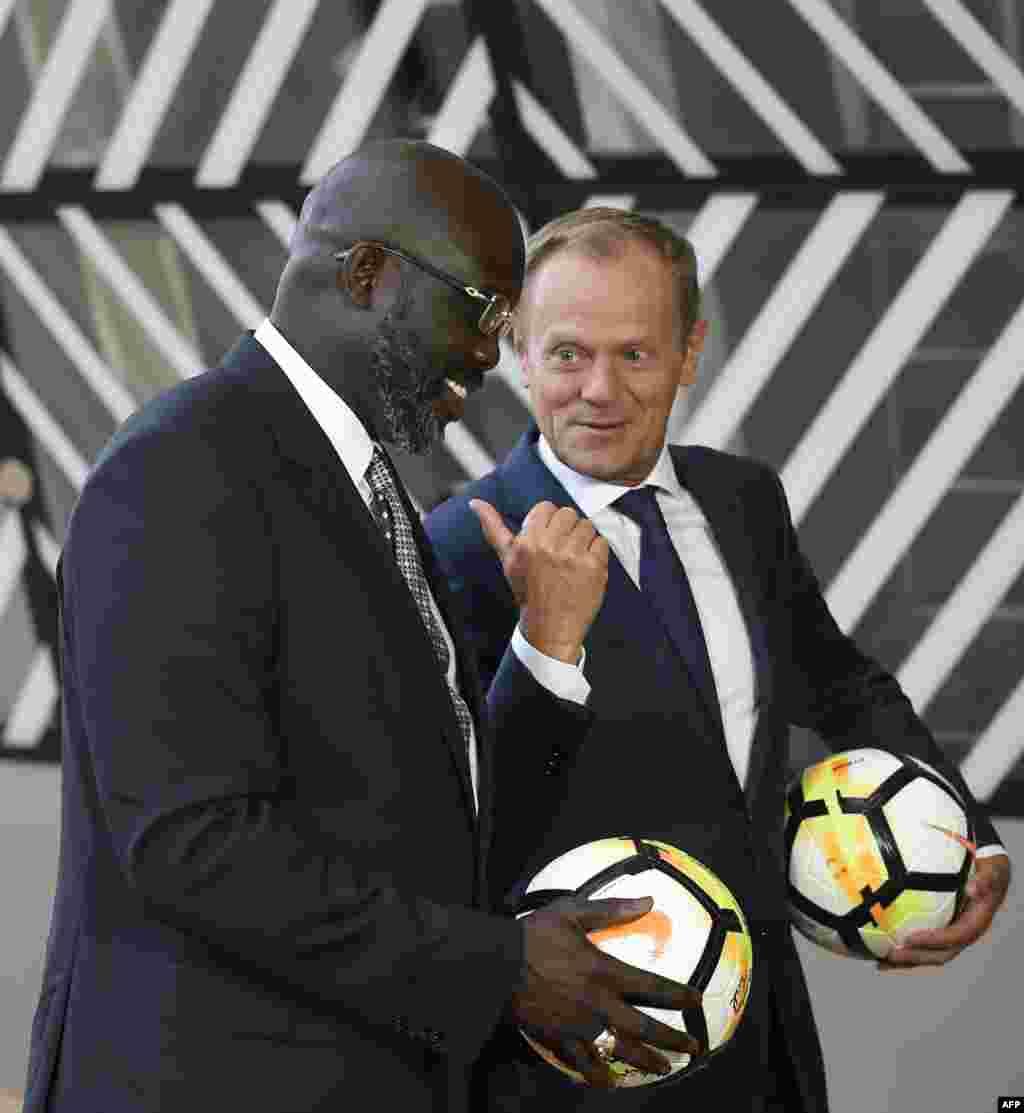 دونالد تاسک، رئیس شورای اتحادیه اروپا و رئیس جمهوری لیبریا با توپ های فوتبال در دستشان پیش از آغاز نشست در مقر اتحادیه اروپا در بروکسل