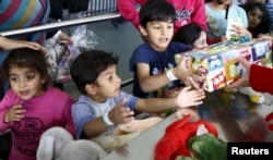 FILE - Migrant children reach out for gifts donated by the local community for the Bayram festivities at an improvised temporary shelter in a sports hall in Hanau, Germany, Sept. 24, 2015.