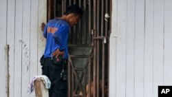 Penjaga keamanan berbicara pada tahanan di dalam sel. Para tahanan ini adalah budak-budak yang berisiko kabur dan hanya diberi sedikit makanan. (AP/Dita Alangkara)