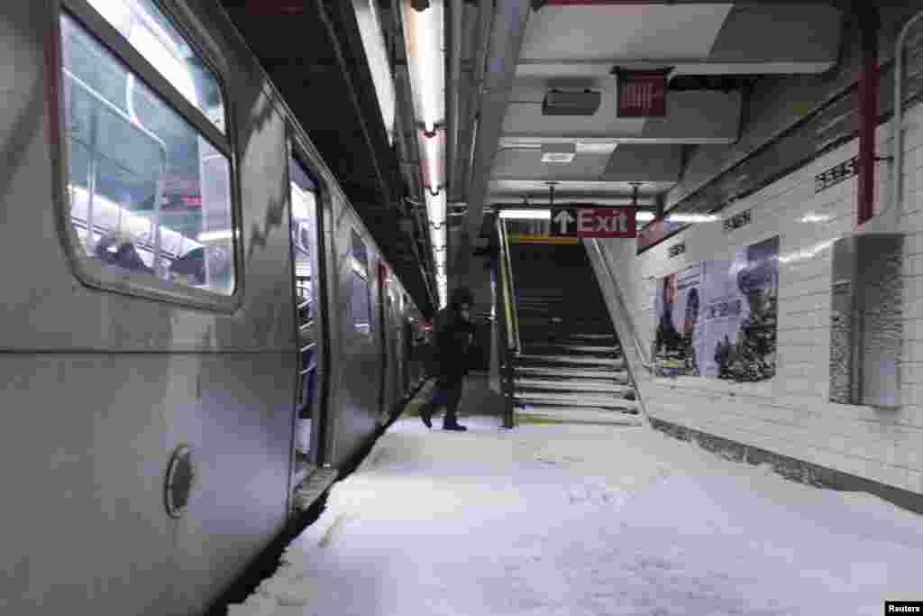 Snow makes it way down to the platform of the 65th Street subway station in New York, Jan. 3, 2014.