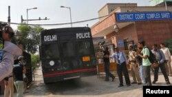 Xe cảnh sát chở 4 người đàn ông bị truy tố về tội cưỡng hiếp và giết hại một phụ nữ 23 tuổi hồi ngăm ngoái trên một chiếc xe buýt hồi năm ngoái.