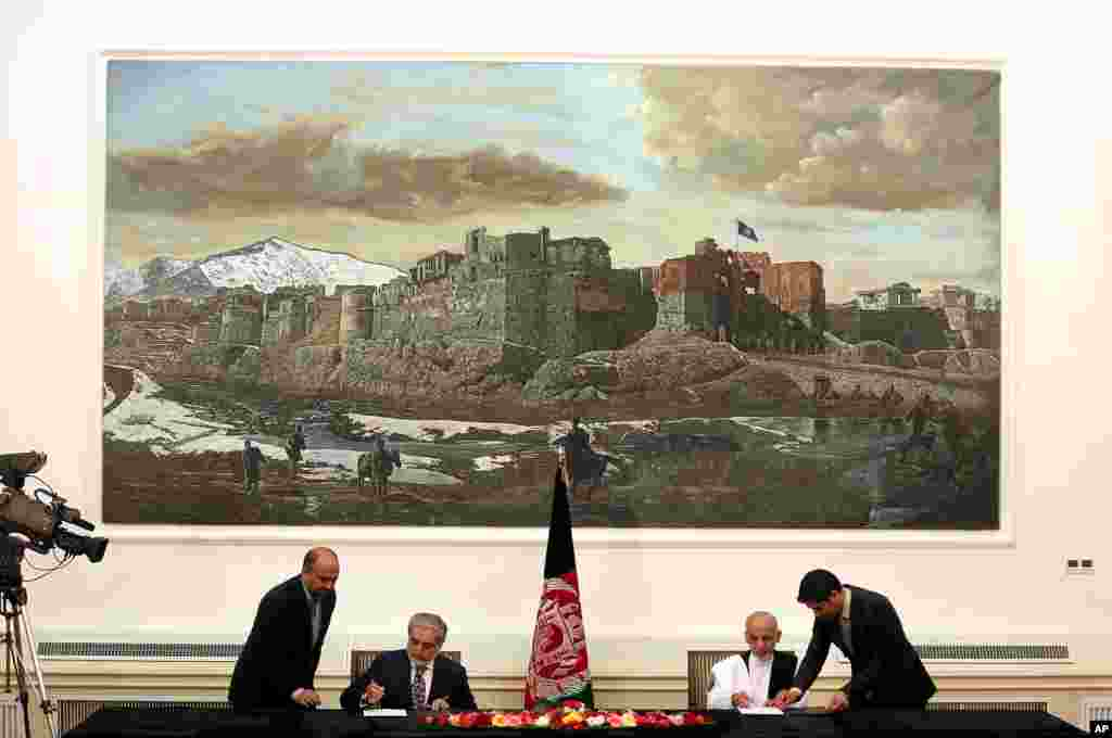 Abdullah Abdullah and Ashraf Ghani Ahmadzai sign a power-sharing deal at the presidential palace in Kabul, Afghanistan, Sept. 21, 2014.