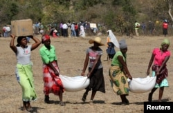 FILE - Villagers collect their monthly food aid provided by United Nations World Food Programme (WFP) in Bhayu, Zimbabwe, September 14, 2016.