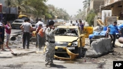 People inspect the aftermath of a car bomb attack in Baghdad's Shiite enclave of Sadr City, Iraq, July 23, 2012.