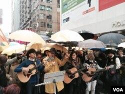 香港流行歌手黃耀明(穿黃色大衣)與何韻詩及多位音樂人,聖誕日在旺角行人專 區街頭演唱,呼籲市民延續雨傘運動精神,繼續爭取真普選