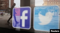 一家商店的櫥窗上映照著推特和臉書的標識。(資料圖片)