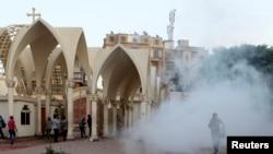 Anggota kelompok Kristen Koptik lari ke dalam katedral di Kairo saat polisi melemparkan gas air mata di tengah perseteruan dengan kelompok Muslim (7/4). (Reuters/Asmaa Waguih)