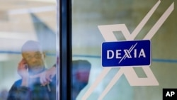 A man looks out of a door next to the Dexia logo at the corporate headquarters in Brussels, October 4, 2011.