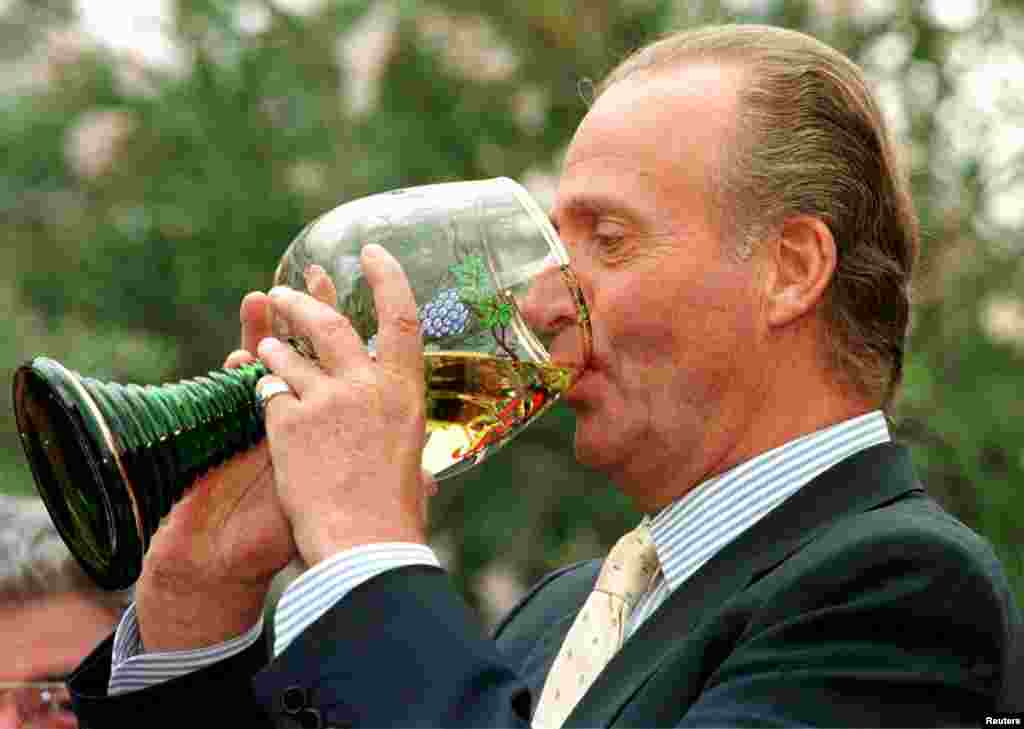 Spanish King Juan Carlos drinks wine out of a large traditional glass of Germany's Rhineland-Palatinate area during a visit in Deidesheim, Germany, July 17, 1997.