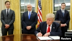 U.S. President Donald Trump, flanked by Senior Advisor Jared Kushner (standing, L-R), Vice President Mike Pence and Staff Secretary Rob Porter signs his first executive orders in the Oval Office Jan. 20, 2017. (REUTERS/Jonathan Ernst )