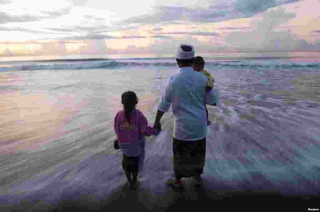 在印度尼西亚巴厘岛的吉安雅海滩,一家人站在海滩上,参加在安宁日前一天举行的净化仪式。在安宁日那天,巴厘岛的印度教徒进行一天的打坐和斋戒,不能工作、烹调、点灯,也不能参加任何活动。
