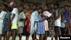 FILE - Liberian children queue for their measles vaccinations in an International Rescue Committee clinic in Monrovia, August 26, 2003.