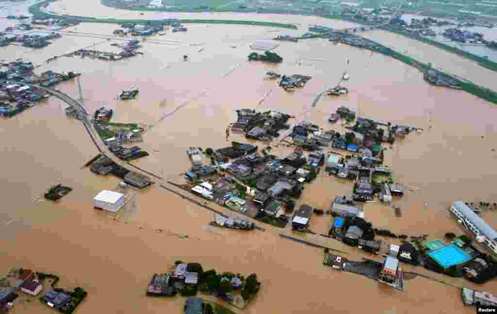 An aerial view shows flooded residential area after a bank of the Yabegawa river collapsed caused by heavy rains in Yanagawa, Fukuoka prefecture.