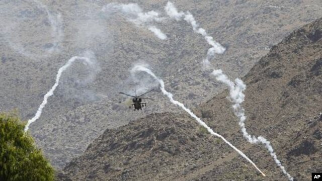 A helicopter belonging to the NATO-led forces fires flares during fighting between the Afghan and foreign troops and the Taliban insurgents in Shewa district of Nanagarhar province, July 17, 2011