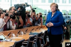 FILE - German Chancellor Angela Merkel, right, arrives for a news conference in Berlin, July 28, 2016. Merkel has not responded to taunts that she would lose reelection by U.S. presidential candidate Donald Trump.