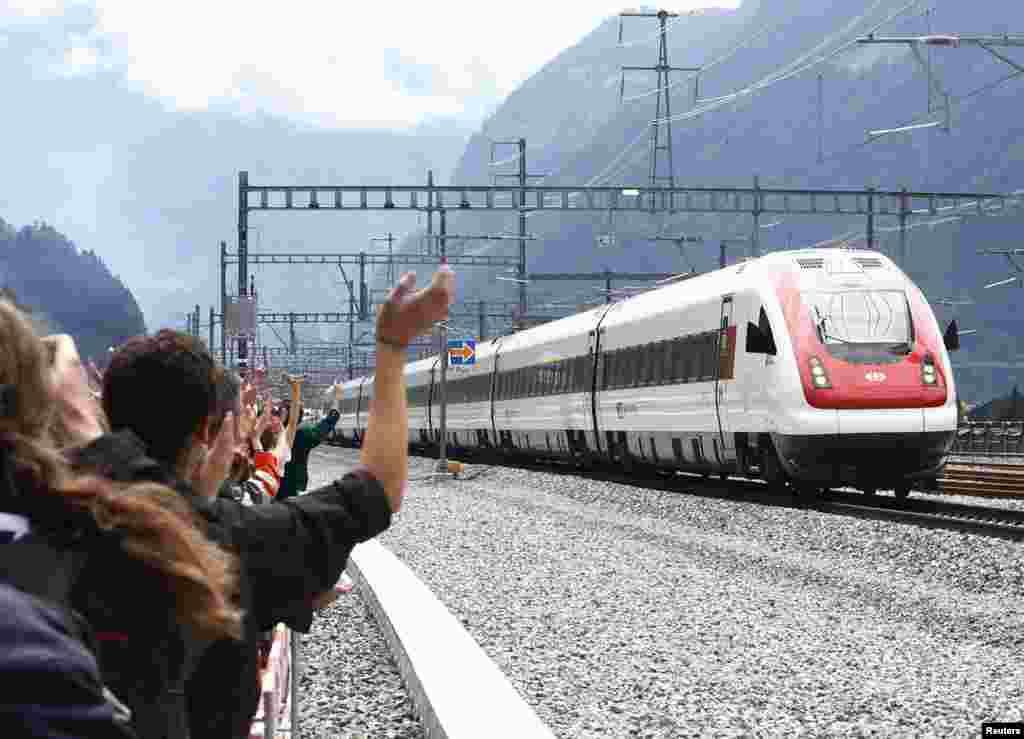 در حاشیه عبور قطار از طولانی ترین تونل جهان، مردم برای سرنشینان قطار دست تکان می دهند. این تونل ۵۷ کیلومتر طول دارد و ۱۷ سال طول کشید تا زیر کوه آلپ ساخته شود.