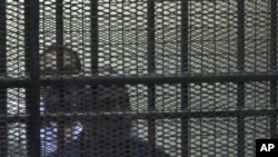Egypt's former Interior Minister Habib al-Adly, front, stands behind bars during his trial on charges relating to the killing of nearly 900 protesters during the 18-day uprising, Cairo, Egypt, July 25, 2011