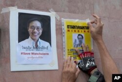 An activist pastes images of Thai dissident Wanchalearm Satsaksit on a wall near Cambodian Embassy in Bangkok, Thailand, Monday, June 8, 2020. (AP Photo)