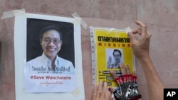 An activist pastes images of Thai dissident Wanchalearm Satsaksit on a wall near the Cambodian Embassy in Bangkok, Thailand, Monday, June 8, 2020. (AP Photo/Sakchai Lalit)