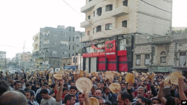 Protesters with pieces of bread shout slogans during a demonstration to show their solidarity with the protesters in Daraa, in the Syrian port city of Banias, May 3, 2011