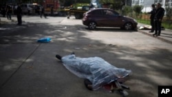 The body of a prison guard lies covered by a plastic sheet outside the Roosevelt Hospital after a shooting, in Guatemala City, Aug. 16, 2017.