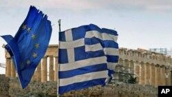 ພາຍໃຕ້ບັນຍາກາດ ທີ່ຈະໄດ້ຮັບເງິນກູ້ຢືມງວດທີສອງ ທຸງຊາດກຣິສແລະທຸງສະຫະພາບຢູໂຣບກໍາລັງປີວສະບັດ ຢູ່ຕໍ່ໜ້າຕຶກ The Parthenon ທີ່ກຸງ Athens ທີ່ 18 ເດືອນກຸມພາ ປີ 2012.