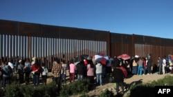 امریکہ اور میکسیکو کی سرحد پر نصب آہنی دیوار کے نزدیک تارکین وطن جمع ہیں۔ (فائل فوٹو)