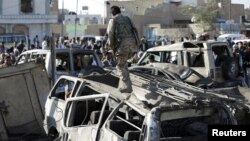 Pemberontak Houthi memeriksa lokasi permukiman yang terkena serangan udara di dekat bandara Sanaa, Yaman (26/3).