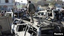 胡塞叛军人员走过被空袭炸坏的汽车。