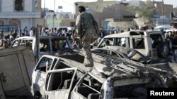 A Houthi fighter walks on a vehicle damaged by an air strike at a residential area near Sanaa Airport March 26, 2015.
