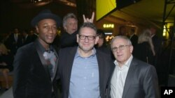 FILE - Singer Jon Bon Jovi photobombs a group photo of, from left, Aloe Blacc, Lucian Grainge and Irving Azoof at a gala in Nov. 5, 2015. (Photo by Matt Sayles/Invision for City of Hope/AP Images)