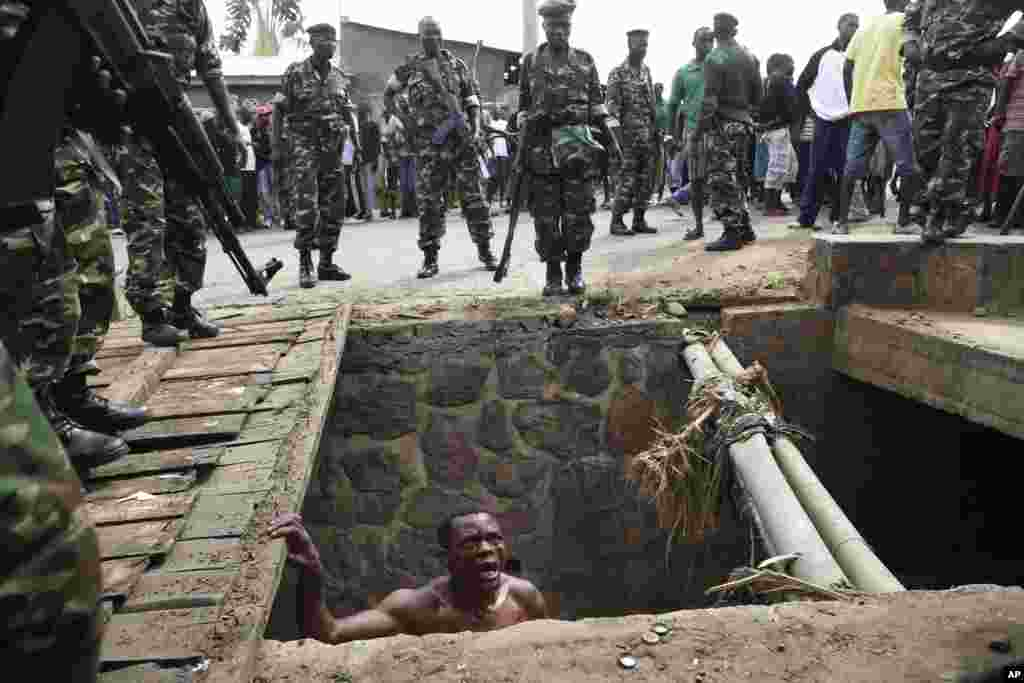 Jean Claude Niyonzima pleads with soldiers to protect him from a mob of demonstrators after he emerged from hiding in a sewer in Bujumbura, May 7, 2015