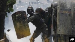 Guardias bolivarianos se defienden del lanzamiento de una lata con materia fecal lanzada contra ellos por manifestantes opositores al régimen.