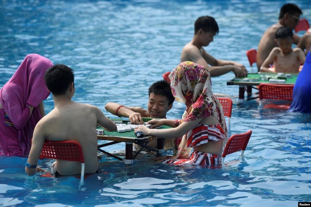 在中国重庆,炎热的一天,人们在水上公园玩麻将。(2017年8月2日)