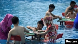 People play mahjong as they sit in water at a water park on a hot day in Chongqing, China August 2, 2017.