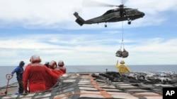 En esta foto de 2011, marineros del USNS Rappahannock llevan ayuda humanitaria a las víctimas del terremoto de Japón. Este mismo buque disparó este lunes a una embarcación sospechosa, en el golfo Pérsico.