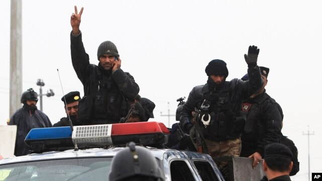 An Iraqi riot police officer flashes the V-sign as his unit returns to its headquarters from clashes between Iraqi army and al-Qaida fighters Basra, Iraq's second-largest city, Jan. 5, 2014.