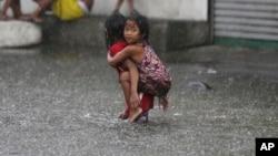 Hai em bé Philippines đi qua vùng lụt lội ở ngoại ô Mandaluyong nằm ở phía đông Manila, Philippines, vì bão Nepartak hôm 8/7.