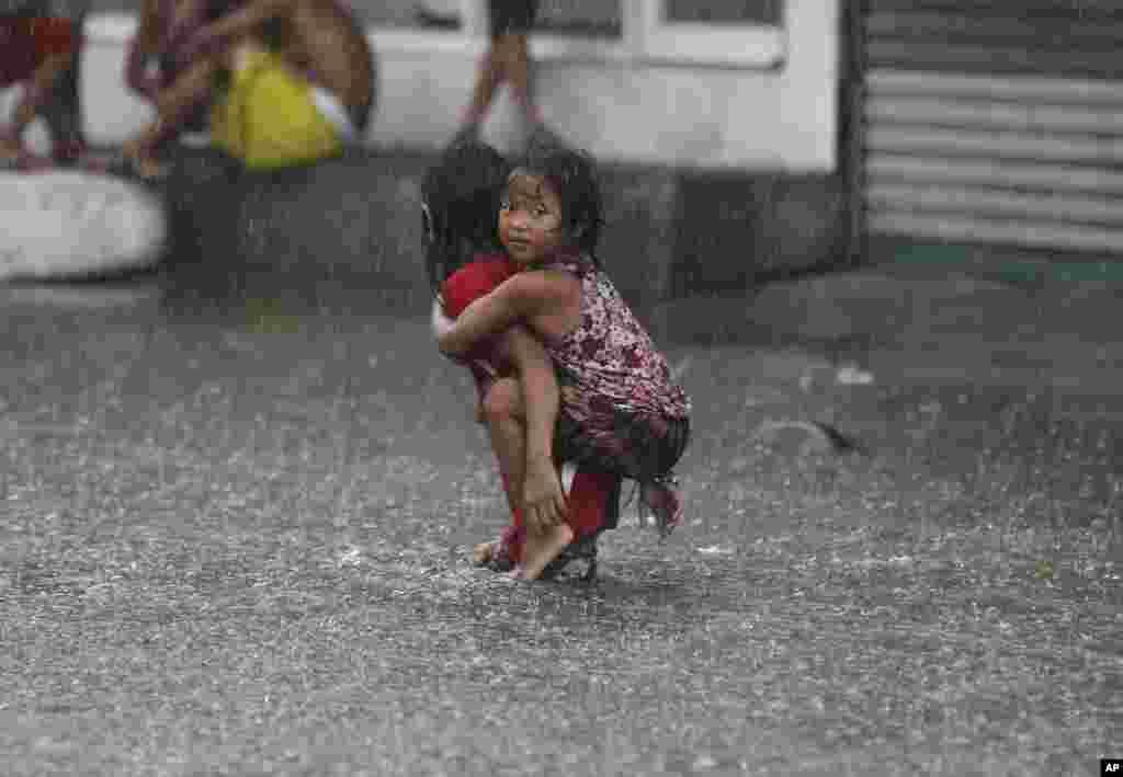 Bé gái Philippines đội mưa lội qua một con đường ngập nước ở vùng ngoại ô Mandaluyong, phía đông thủ đô Manila, Philippines. Mưa mùa tiếp tục hoành hành sau khi bão Nepartak quét qua Philippines.