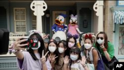 Vizitorët në Disneyland bëjnë fotografi me personazhet e mirënjohur të filmave vizatimorë (Hong Kong, 25 shtator 2020)