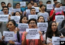 FILE - Filipino student activists shout slogans as they call for justice for victims of extrajudicial killings during a rally at the University of the Philippines in suburban Quezon city, north of Manila, Philippines, Aug. 11, 2016.