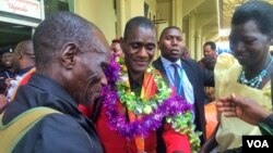 David Emong's parents wrap garlands around his neck at Entebbe International Airport, welcoming him back to Uganda after his Paralympics win. (L. Paulat/VOA)