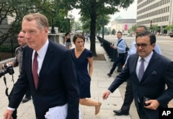 United States Trade Representative Robert Lighthizer, left, and Mexican Secretary of Economy Idelfonso Guajardo, right, walk to the White House, in Washington, Aug. 27, 2018.