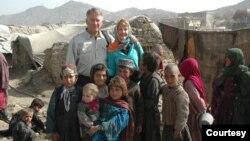 拉米亚阿富汗基金会创始人,退休美国空军中将约翰·布莱德利和妻子简·布莱德利在阿富汗与当地孩子们在一起。(照片由拉米亚阿富汗基金会提供)