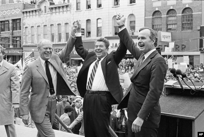 FILE - Former president Gerald Ford, left, lends his support to fellow Republican and presidential candidate Ronald Reagan and running mate George Bush, seen here on the final day of campaigning in Peoria, Ill., Nov. 3, 1980.