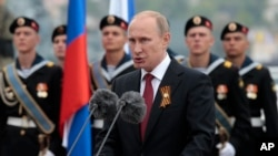 Rossiya rahbari Vladimir Putin Qrimdagi harbiy paradda so'zlamoqda. 2014-yilning 9-mayi. Sharqiy Yevropa davlatlari Rossiyani o'z xavfsizligiga tahdid deb ko'rishi tufayli NATO kengayishi yana ko'tarilmoqda.