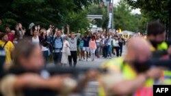Polisi mengawal evakuasi orang-orang dari pusat perbelanjaan Olympia Einkaufzentrum (OEZ) di Munich, Jerman (22/7), menyusul penembakan di sana.